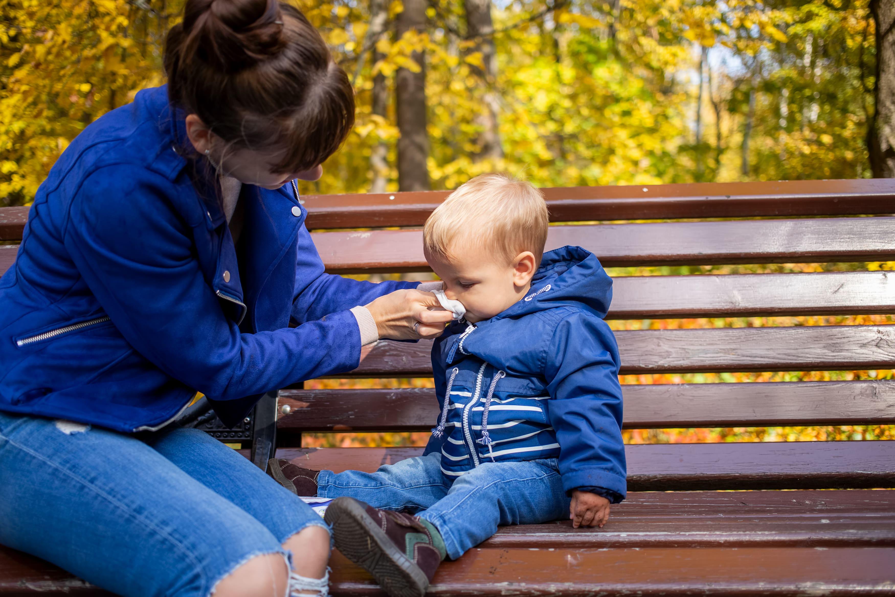 Image représentant une mère aidant son enfant à se moucher en temps d'épidémies hivernales